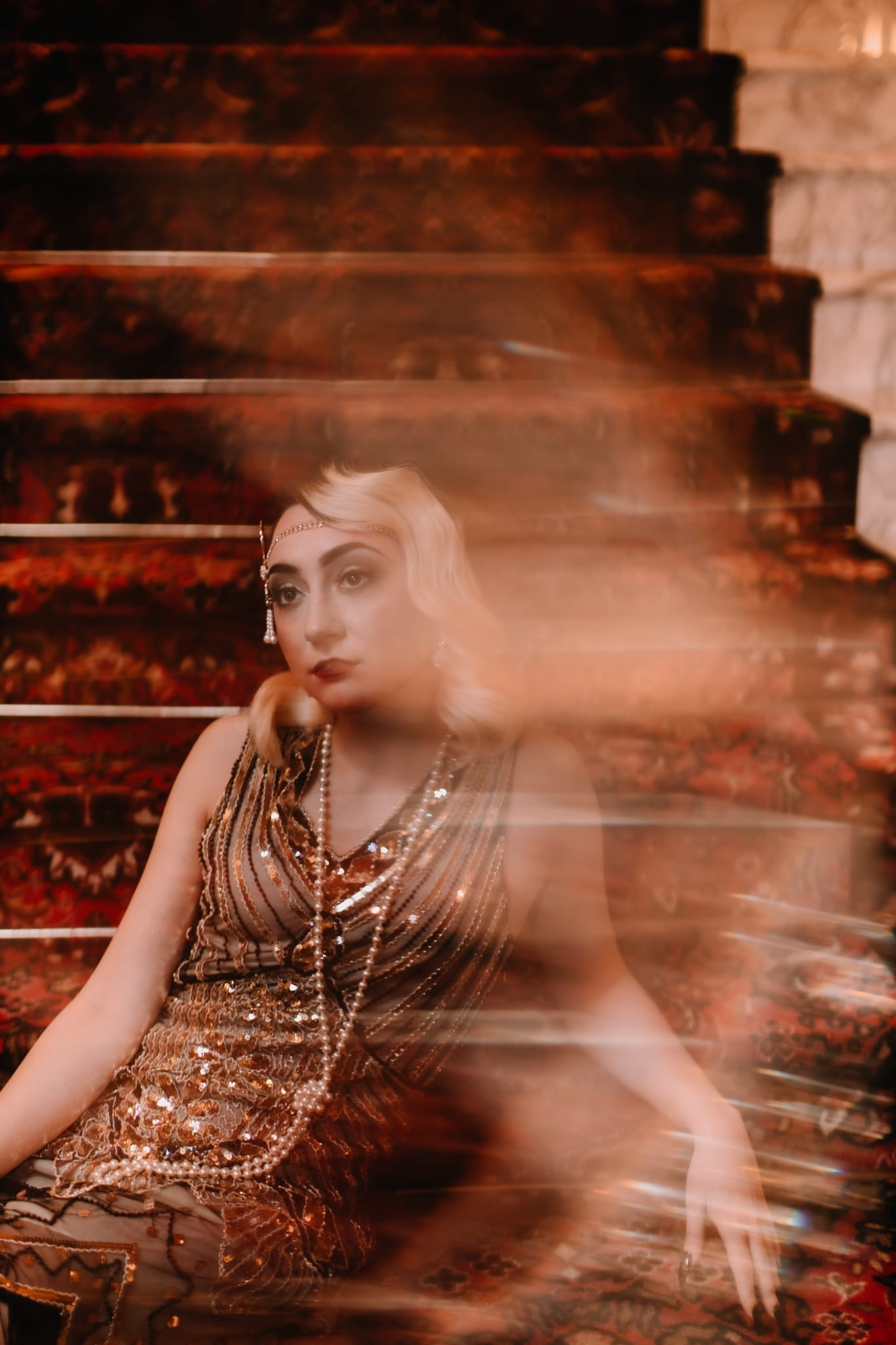 A BLONDE WOMEN IN 20'S THEMED DRESS WITH PEARLS ON A STAIR CASE IN ATLANTIC CITY SHOT BY MEERLOO PHOTOGRAPHY