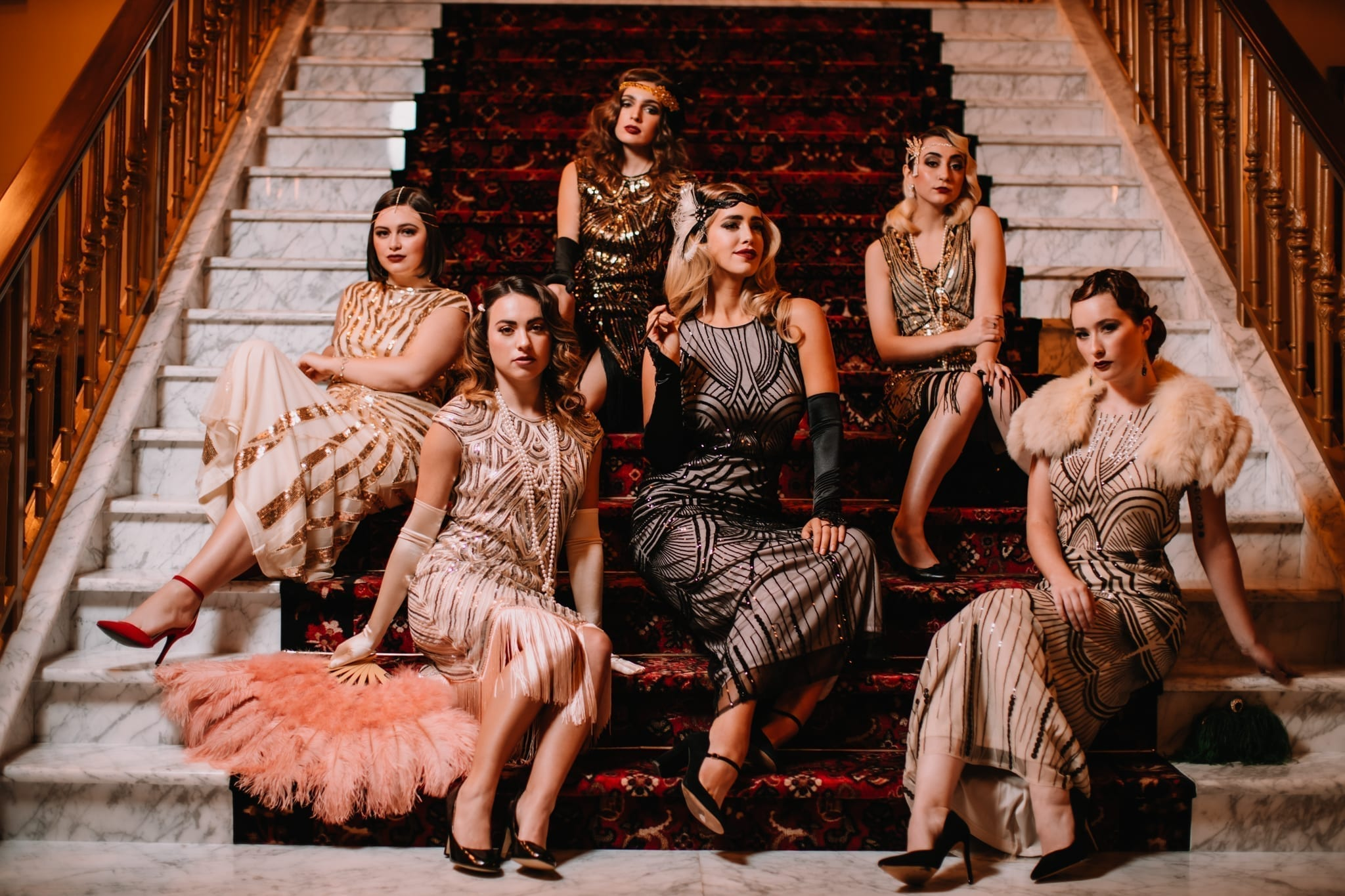 A GROUP OF FIVE WOMEN WEARING 20S THEMED DRESSES SITTING ON A STAIR CASE IN ATLANTIC CITY SHOT BY MEERLOO PHOTOGRAPHY